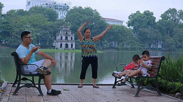 visit hanoi in early morning family at the lake