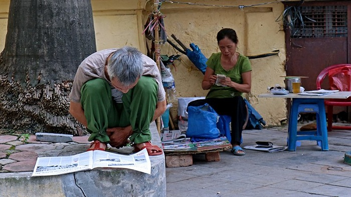 visit hanoi in early morning reading newspaper